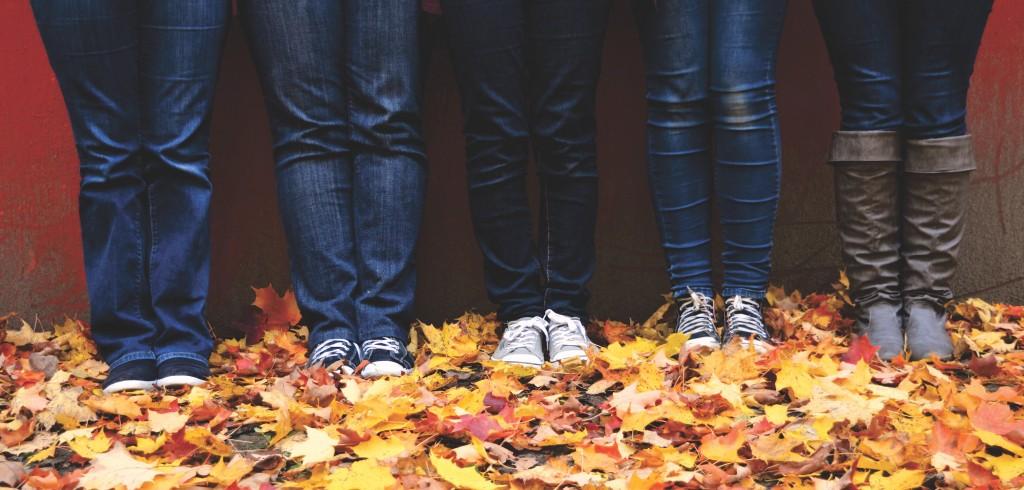 feet standing on autumn leaves