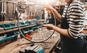 woman holding wheel in bike shop
