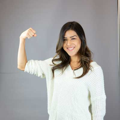 yasmin flexing her muscles with grey background